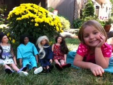 picture dolls by tree with little girl